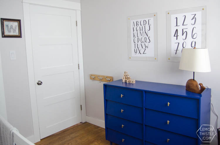 This bold blue dresser with brass hardware is perfect! And I love the floating frames above. Not too 'kiddish'