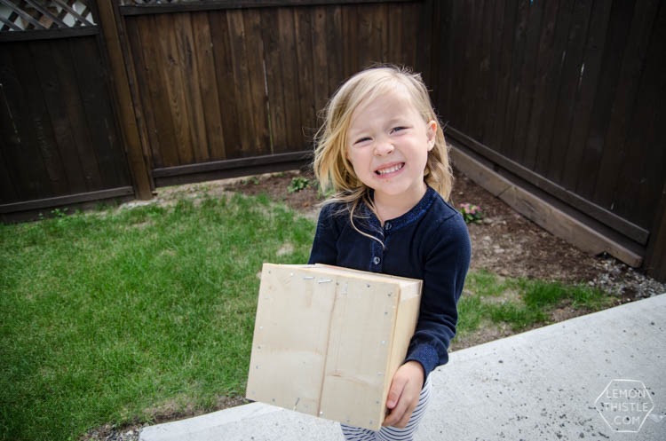 Girl holding wooden box nailed shut with gift card inside
