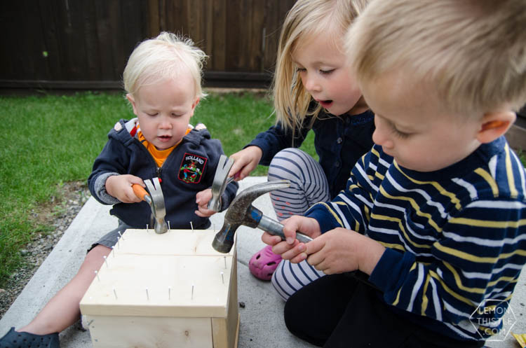 Kids hammering nails to close a wooden crate with gift card inside