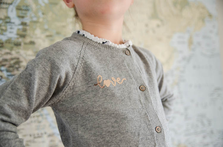 Girl wearing grey cardigan with DIY love design from rose gold foil vinyl