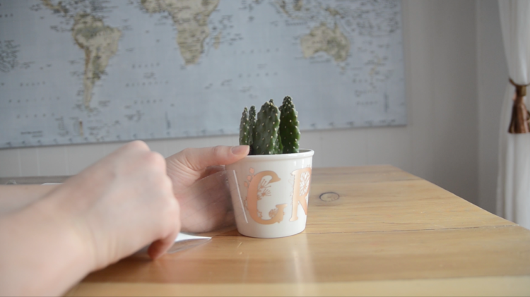 smoothing down matte adhesive foil onto a ceramic plant pot- transfers floral monograms that spell 'grow'