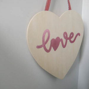 Hanging wood sign in heart shape with pink foil script that reads 'love'