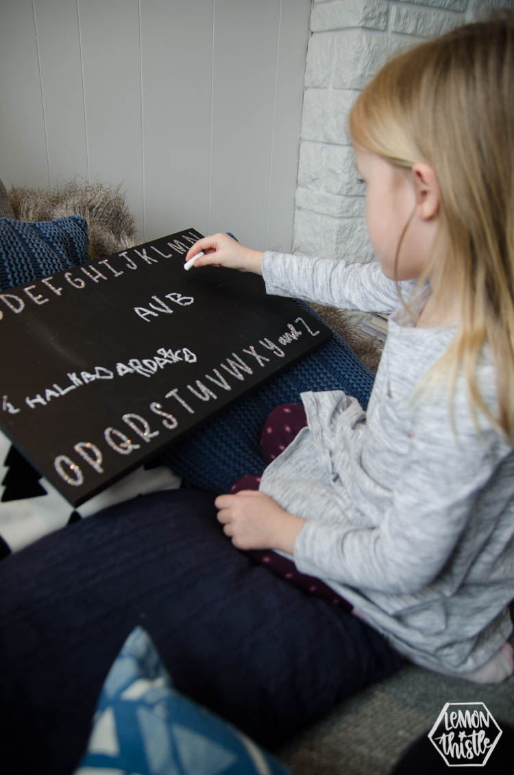 girl using chalkboard to practice letters- glitter vinyl alphabet applied with heat transfer vinyl
