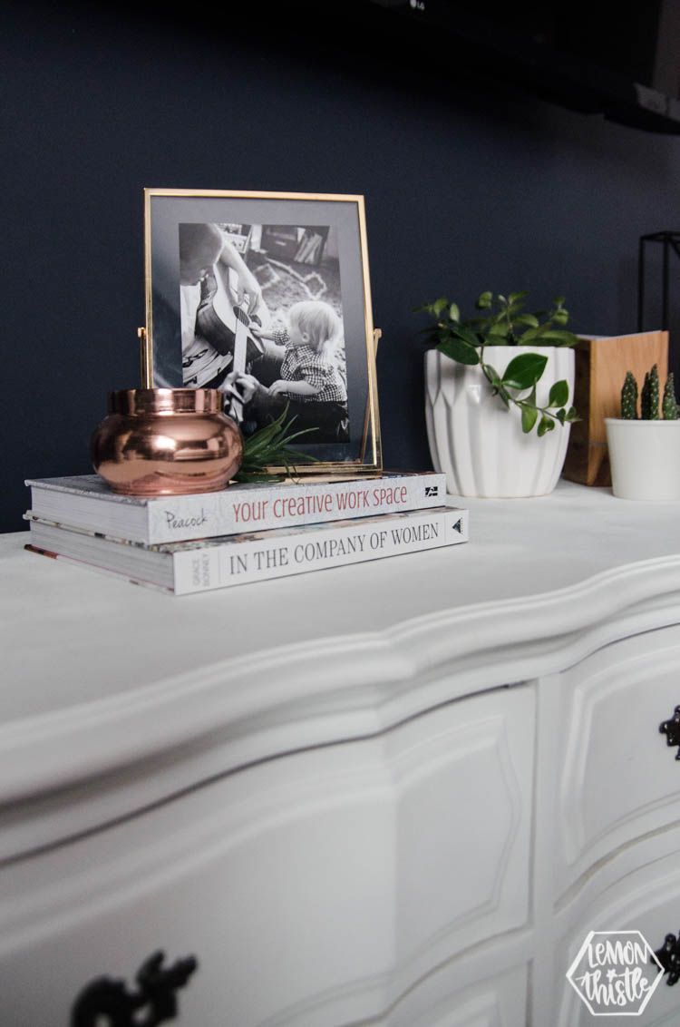 stacked books with candle, faux airplant and photo frame on top of dresser