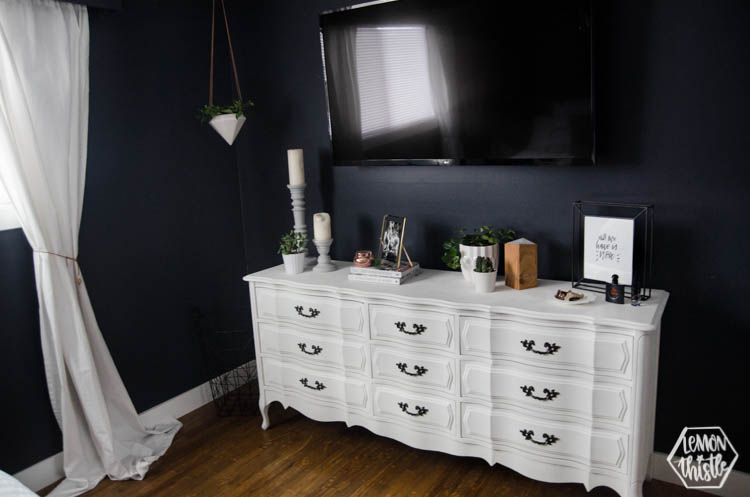 Vintage chalk paint white dresser with TV over in navy master bedroom