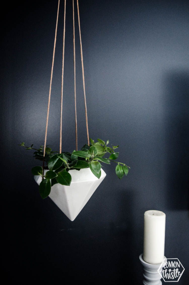 white geometric hanging planter with leather strings in navy bedroom