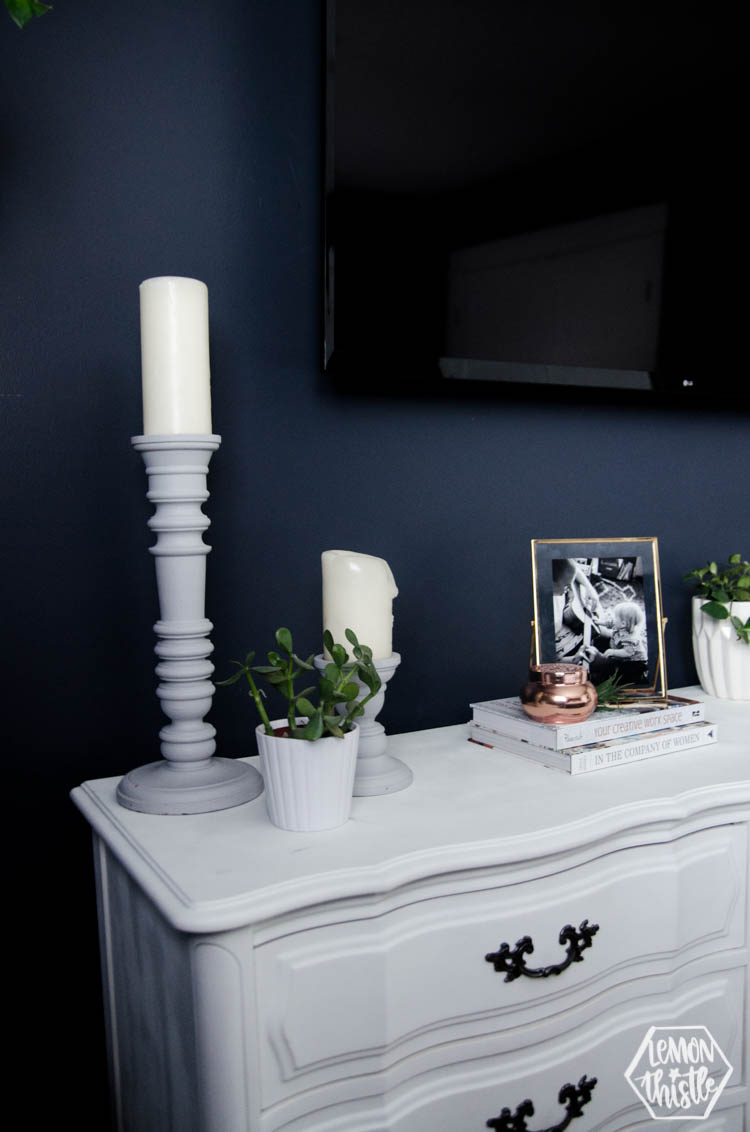 Tall candlesticks help frame the TV above the long dresser.