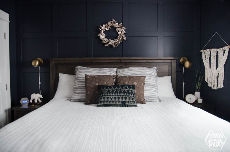 Navy Bedroom with walnut coloured wood headboard and gold sconces above nightstands