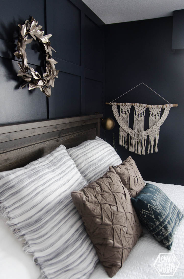 Macrame and metallic wreath decor in navy master bedroom