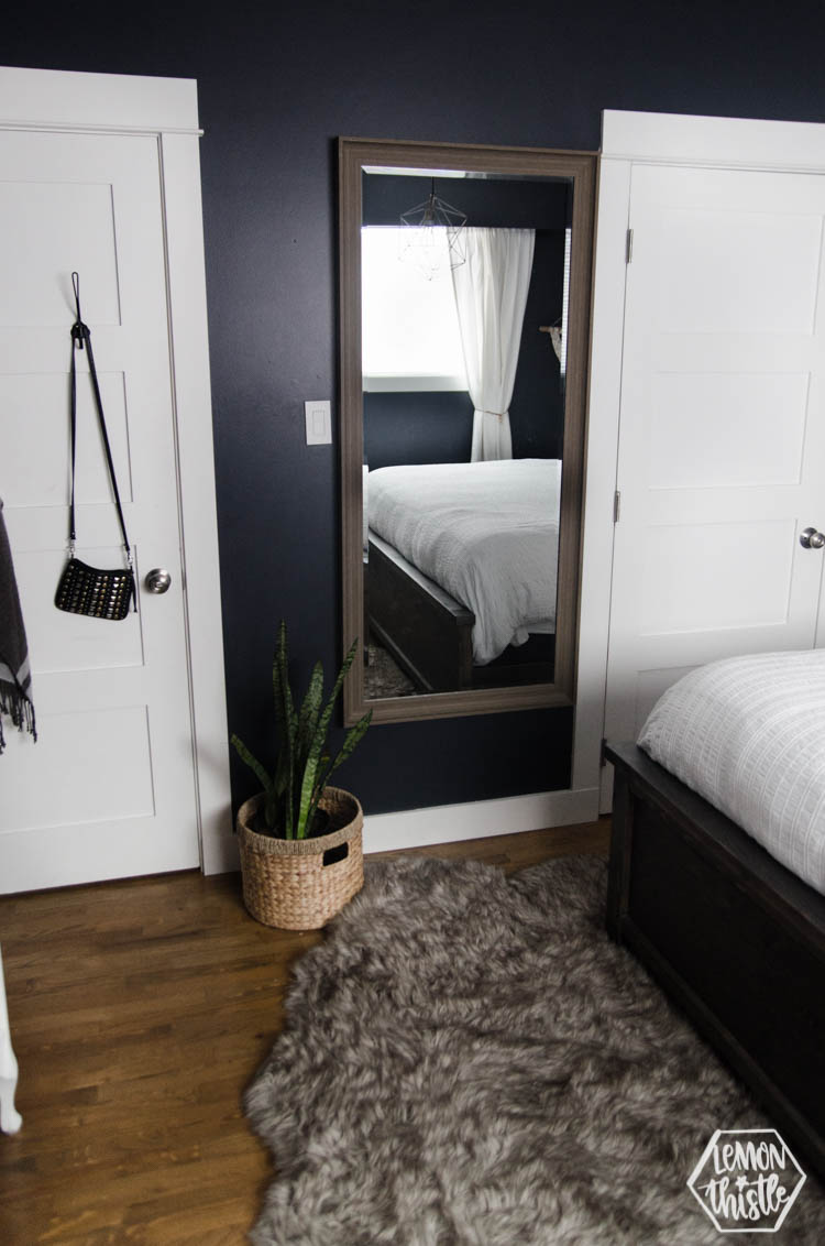 large mirror hung on navy wall in master bedroom- for tight spaces