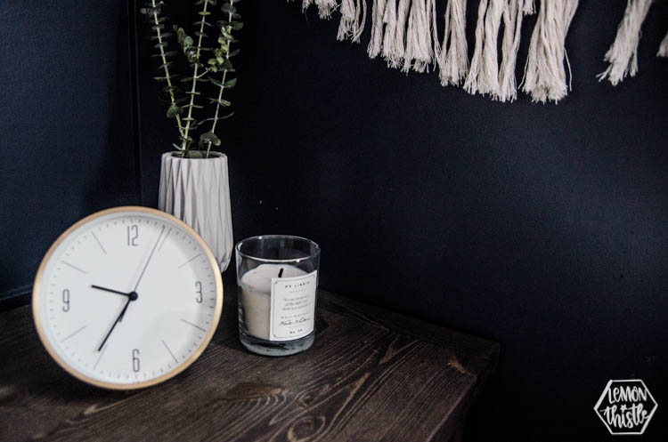 feminine night stand details- gold clock, candle an eucalyptus