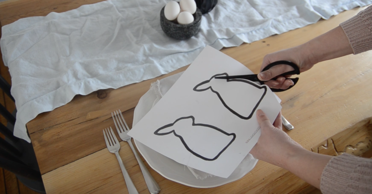 Use scissors to cut out Easter bunny silhouettes for modern place setting