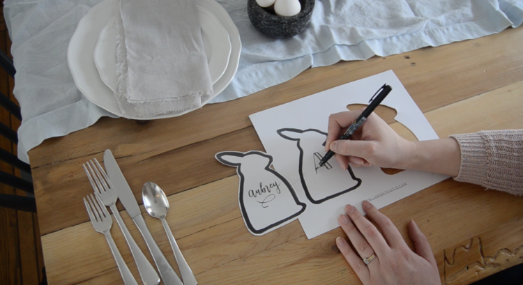 a tombow fude brush pen is used to letter names on bunny shaped place cards for a modern easter table setting