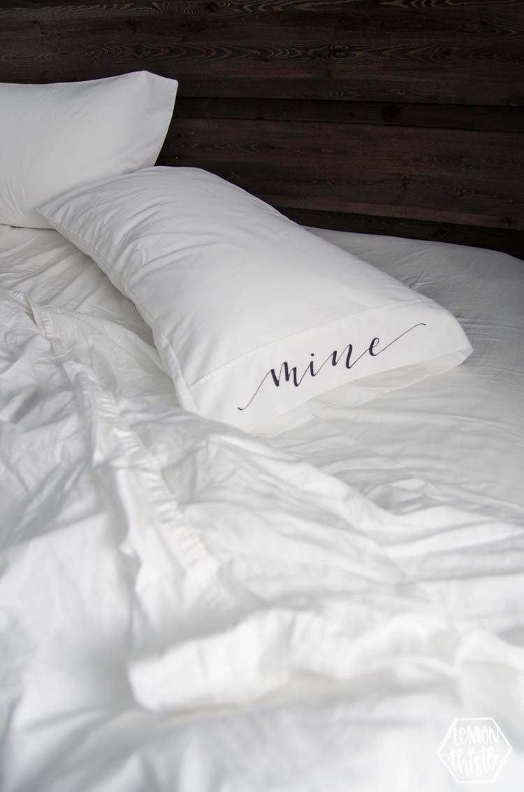 Unmade bed with white pillow case that has black lettering reading, 'mine' (DIY)
