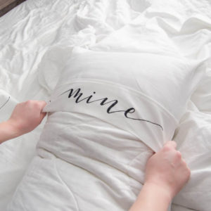 Putting on a king size pillow cover with the lettering 'mine'