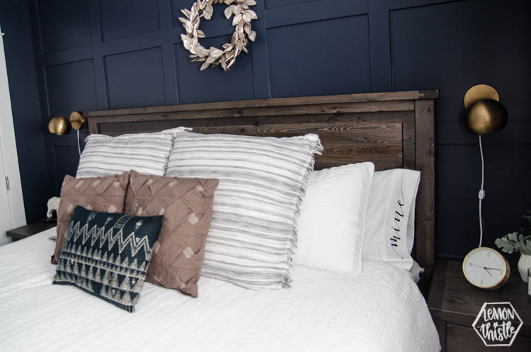 Bed made with white sheets and pillowcases hand lettered 'mine' and 'yours'