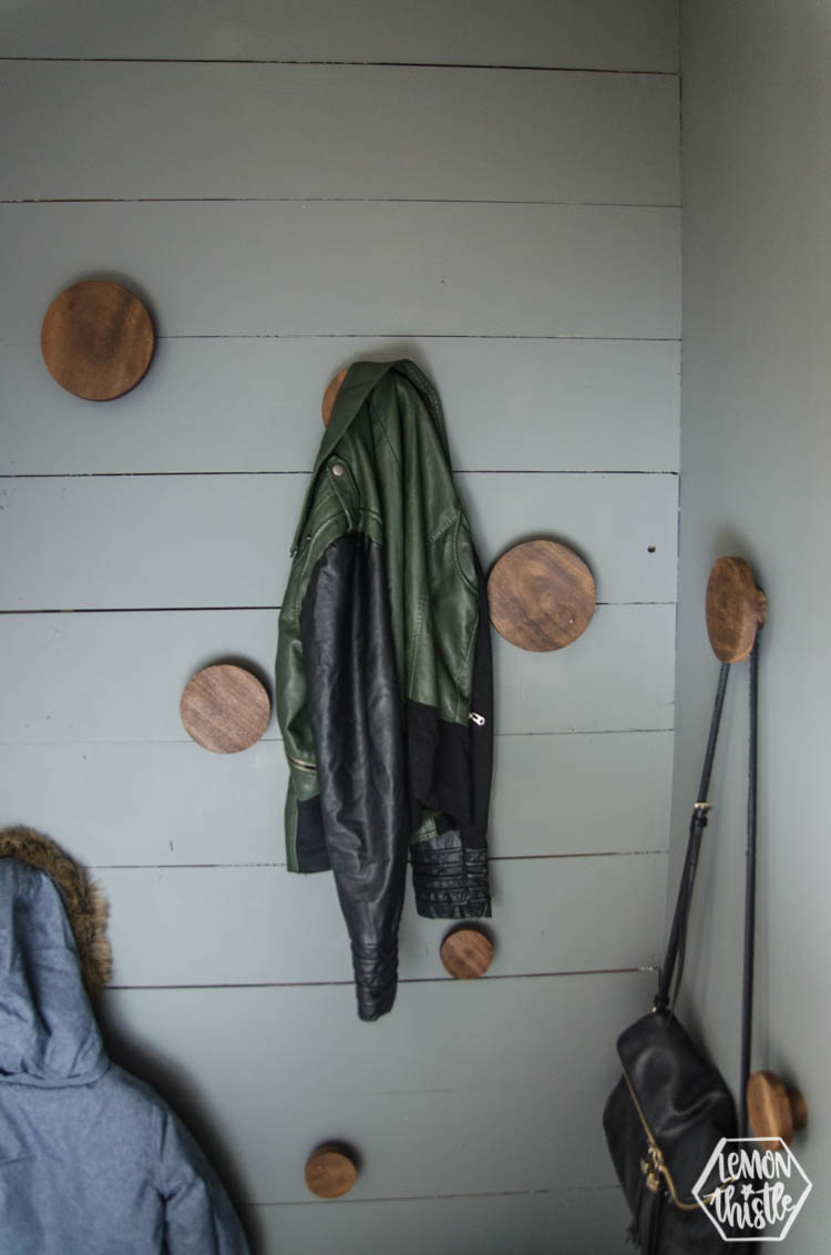 round wooden hooks on a shiplap wall