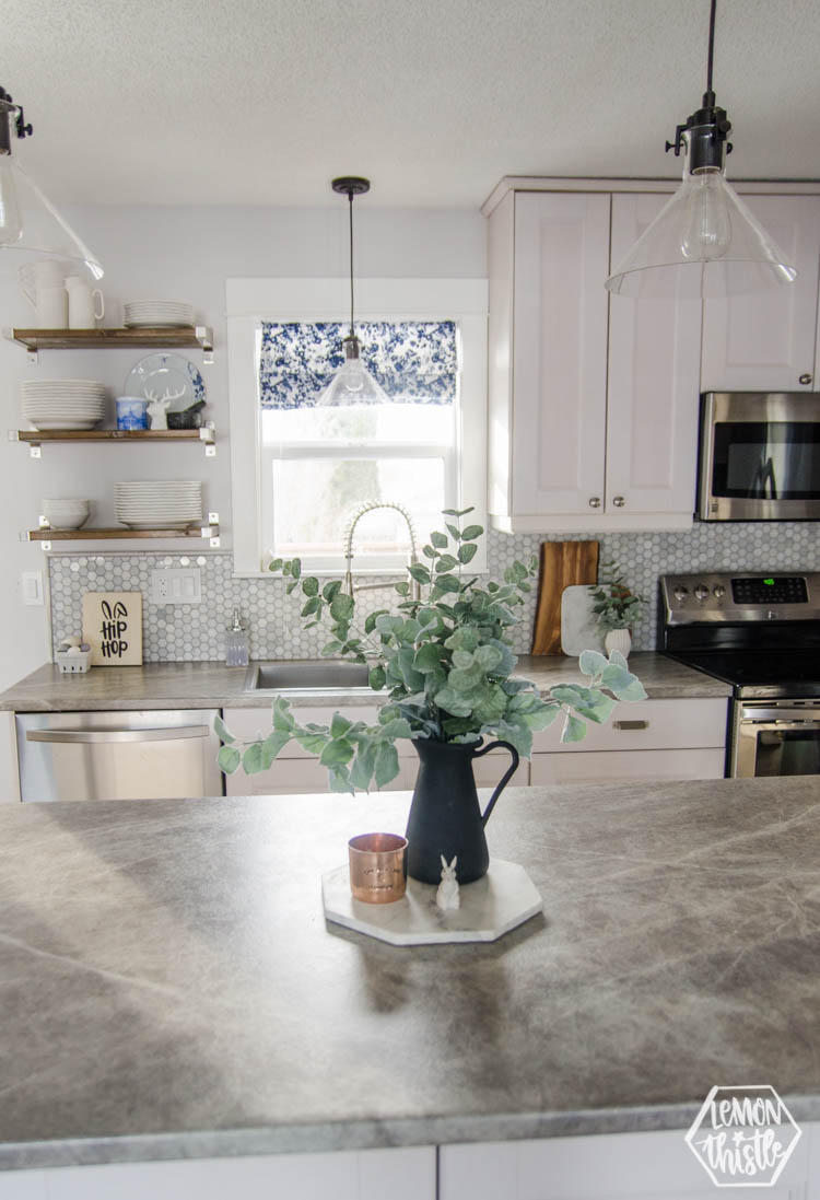 white and grey kitchen with open shelving decorated for spring