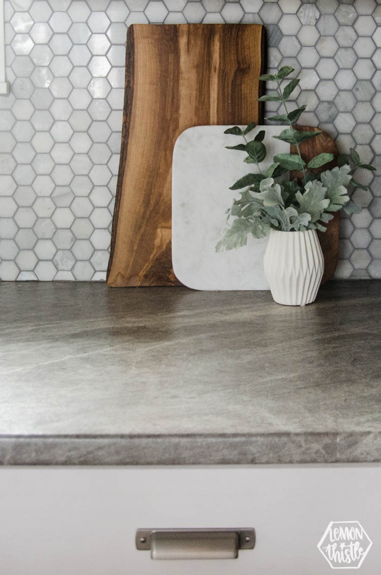 serving boards on counter with vase of greens