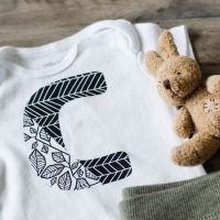 Onesie with large C in two designs of patterned iron on- simple cricut diy