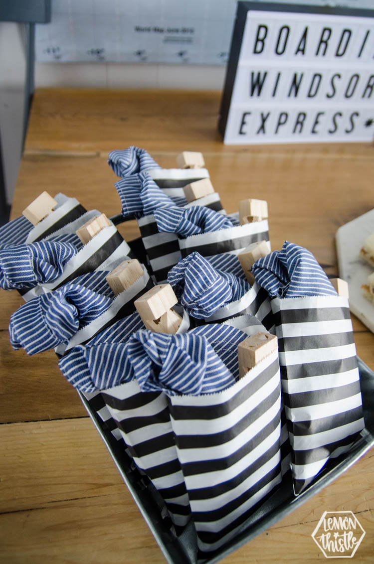 Cute party favours for a train themed party- conductor hats and train whistles in a striped bag