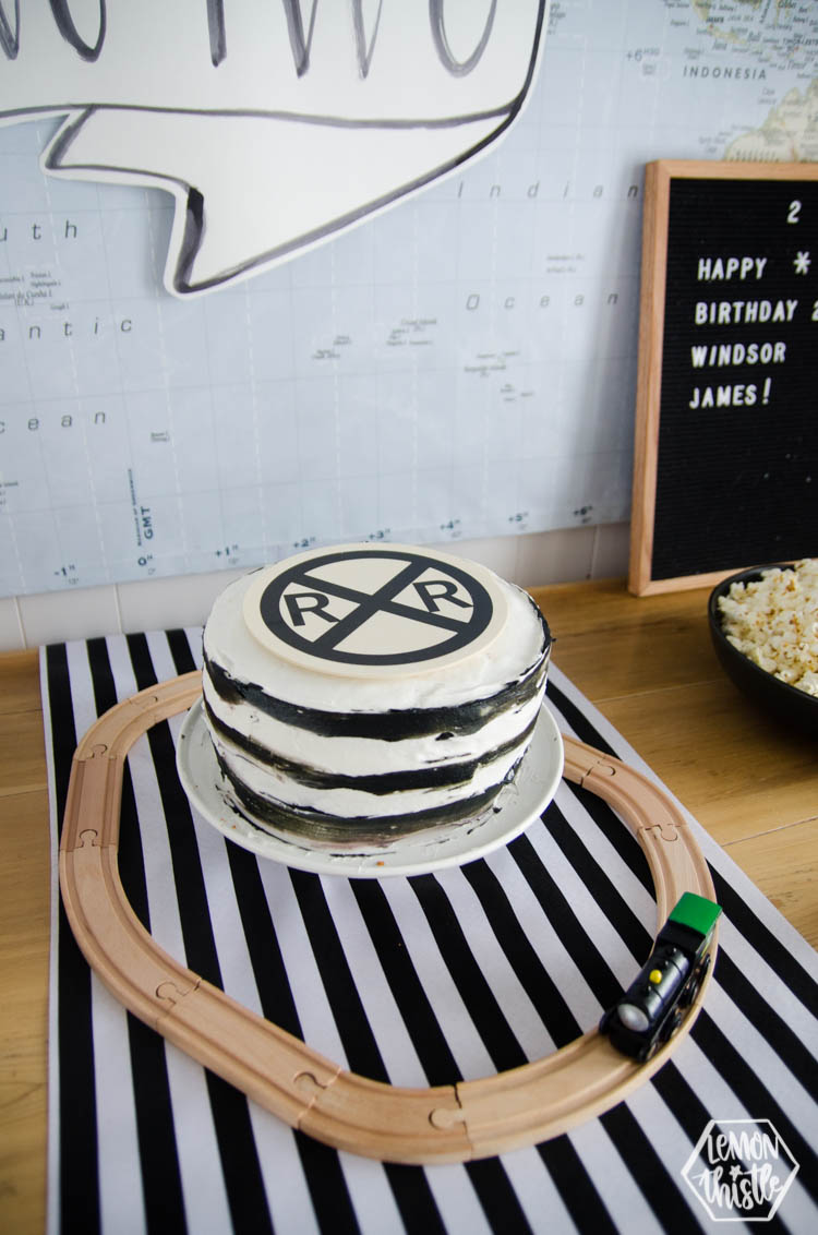 wooden train tracks around cake stand for a train themed birthday party
