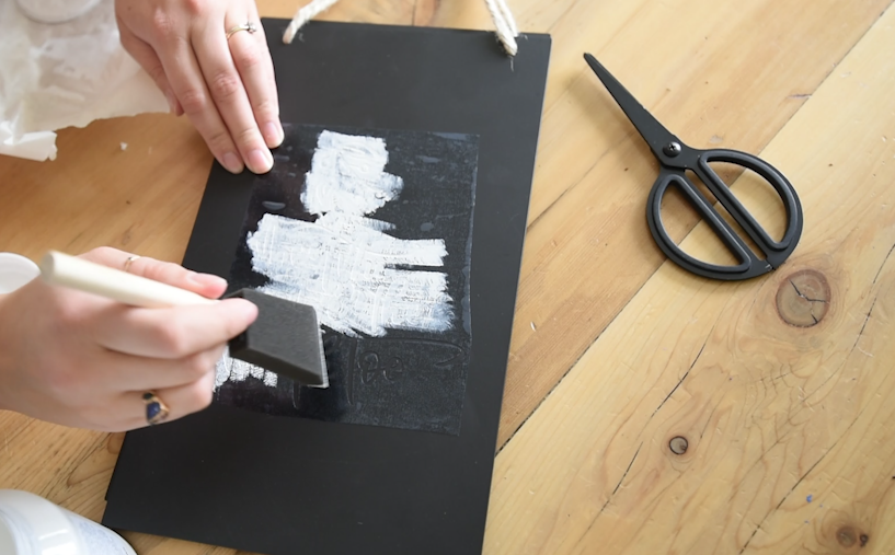 Dabbing paint on a stencil for a chalkboard effect