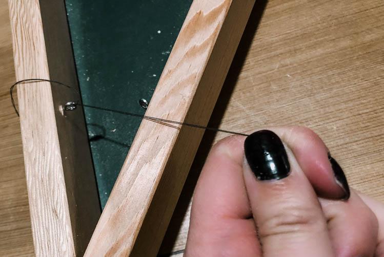 Eye hooks into wood frame