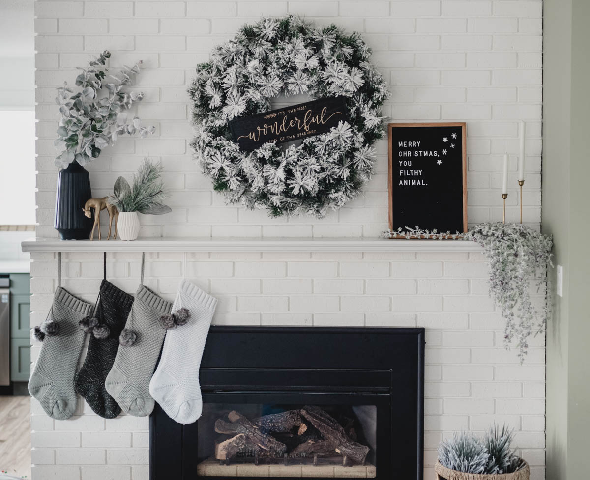 Modern holiday mantel with flocked greenery