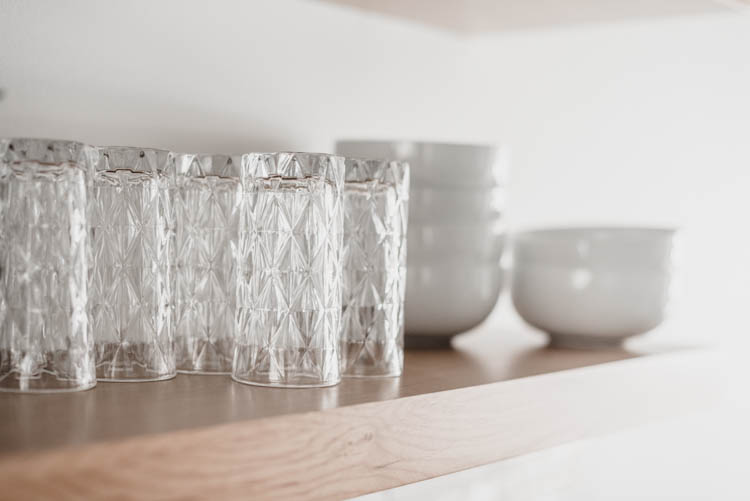 Pretty glasses and plain white dishes for practical but pretty open shelving in the kitchen