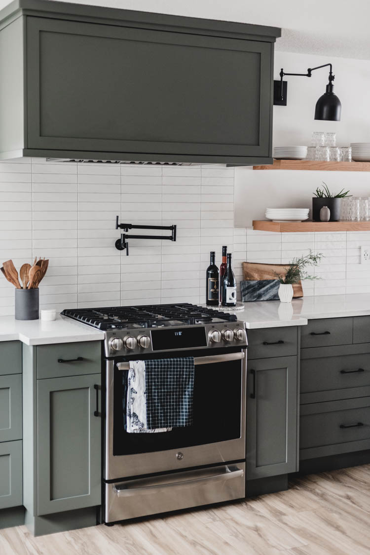 Modern black pot filler with green cabinets... so good!
