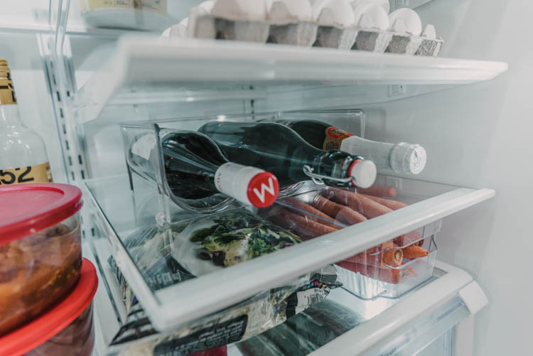 Using a wine bottle holder to free up tall shelf space in fridge