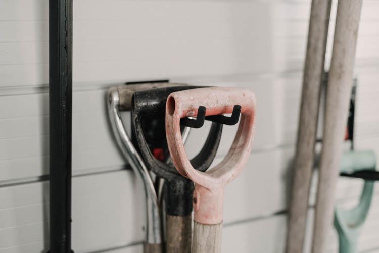 One slat wall hook holding 3 shovels