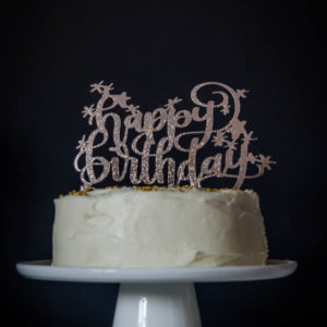 Happy Birthday glittery cake topper on white iced cake