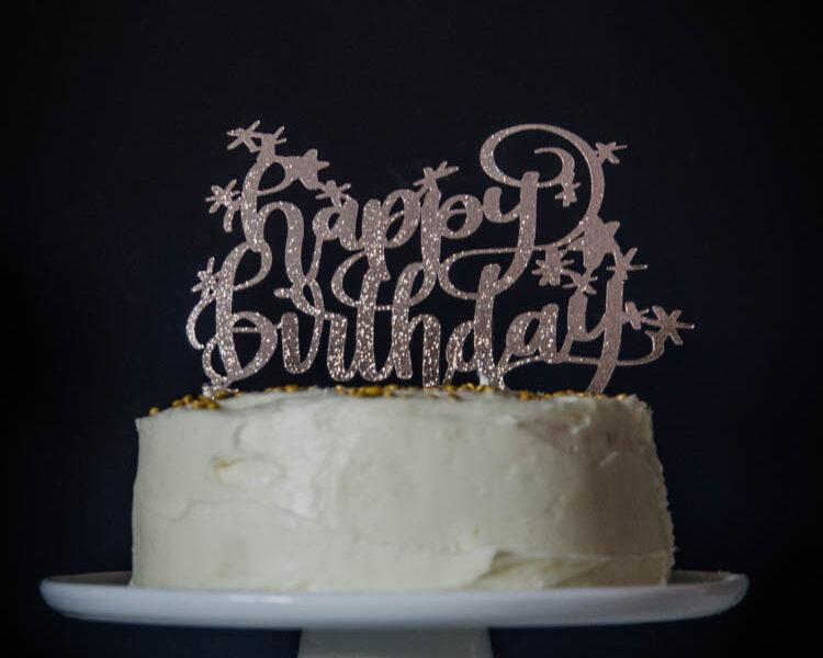 Happy Birthday glittery cake topper on white iced cake