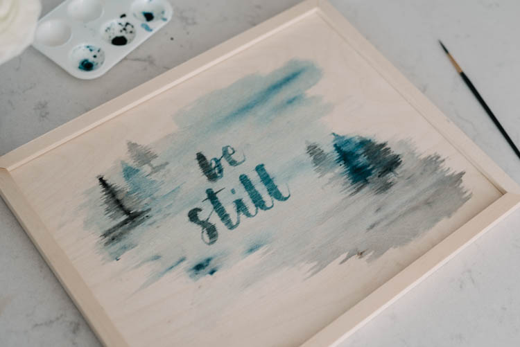 Be Still hand lettering over foggy trees watercolour painting on wood