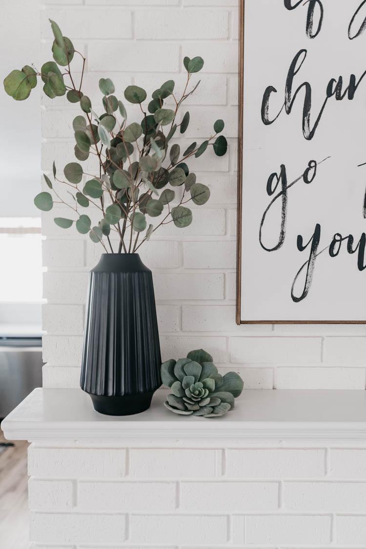 Black vase full of silver dollar eucalyptus on white brick fireplace