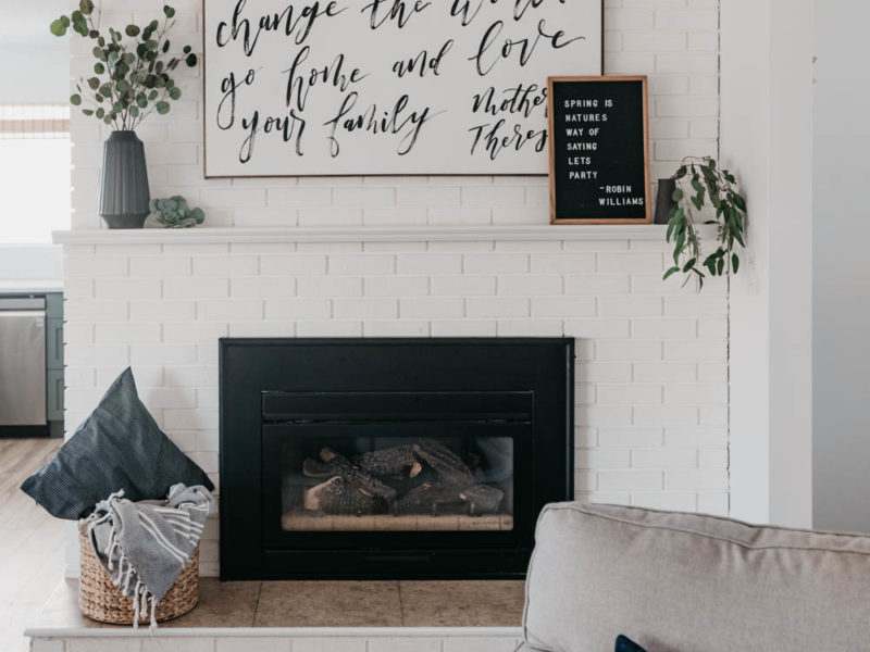 white brick fireplace decorated with black vases and white details, hand lettered art and letterboard reads 'spring is nature's way of saying let's party' - robin williams quote