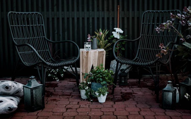 Modern brick patio- love the black wicker chairs!