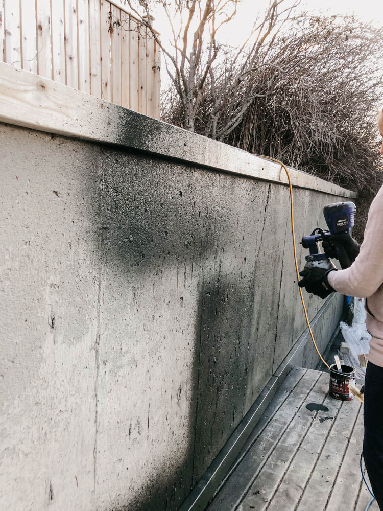 Painting a concrete wall with a paint sprayer- to build a DIY patio screen!