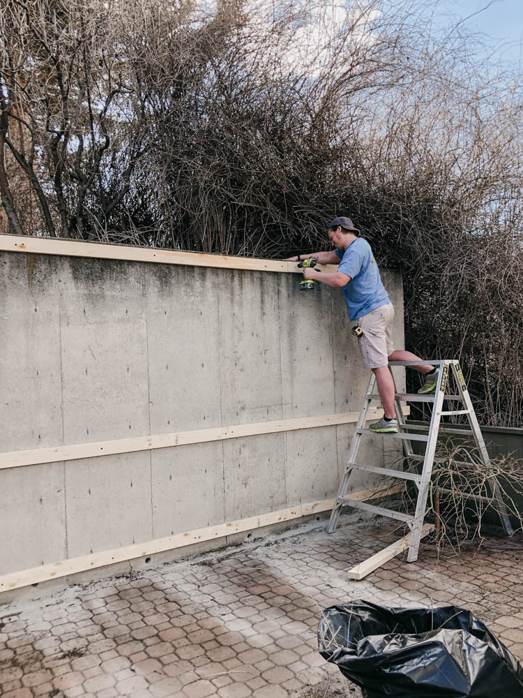 Attach 2x4s to concrete wall to attach wood slats to