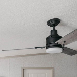 Beautiful farmhouse style fan on a sloped ceiling- great tips to install it on an angled ceiling