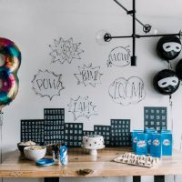 Tablescape with cartoon buildings and word bubbles for superhero birthday party