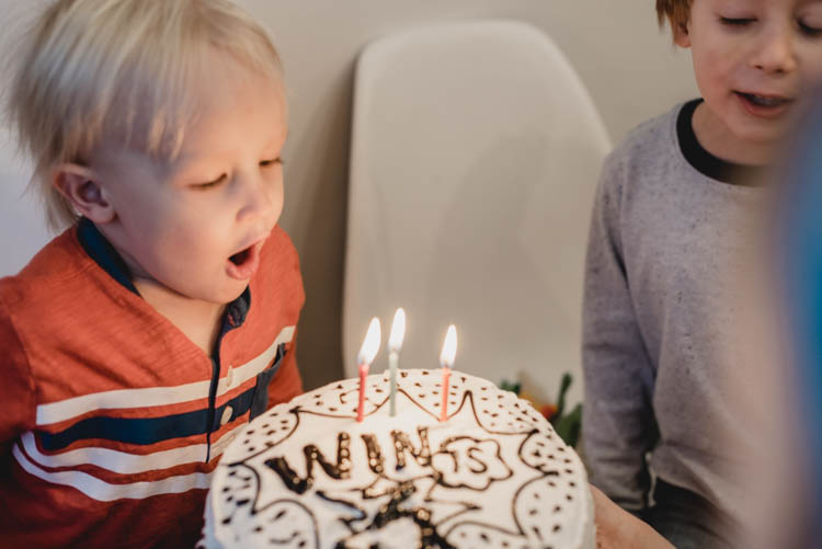 three year old blowing out candles on his super hero cake