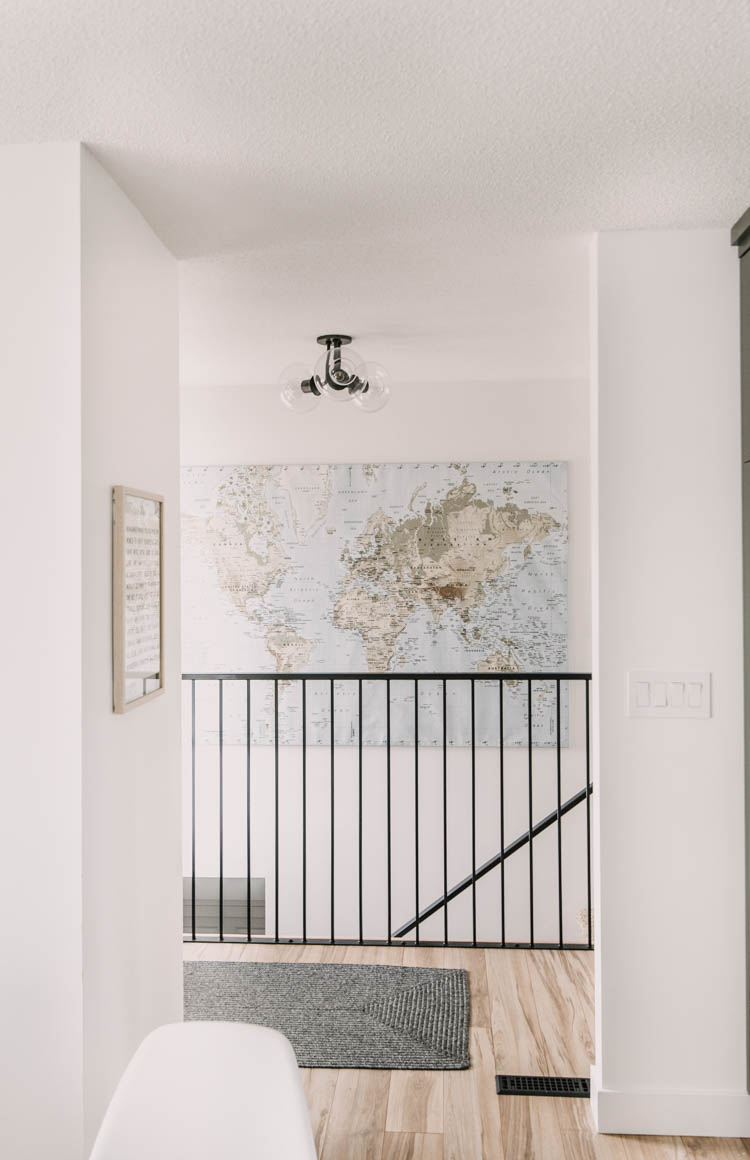 Modern Entryway Makeover- love the giant map over the stairs wall... those big walls are so hard to decorate!