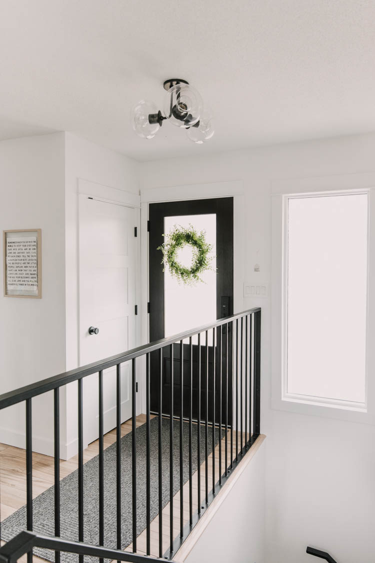 Modern metal stair railing in a small entryway makeover