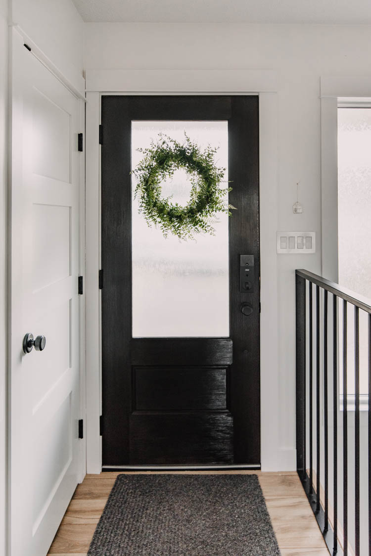 Black Door in the entry way with 3/4 glass