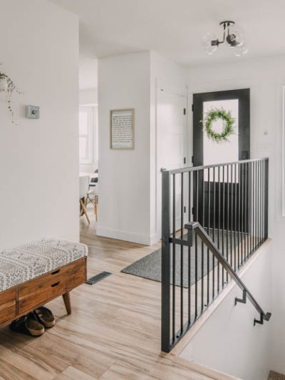 Bright white entry way makeover with black door and metal railing... plus that storage bench!
