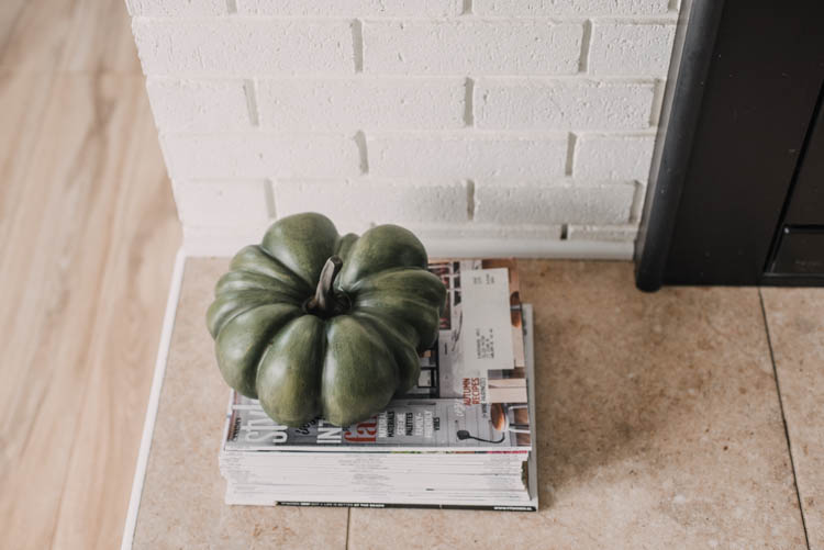 Heirloom faux pumpkin on stack of magazines