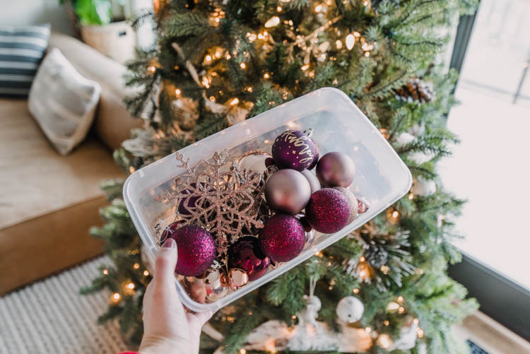 Adding rose gold and burgundy ornaments to the christmas tree